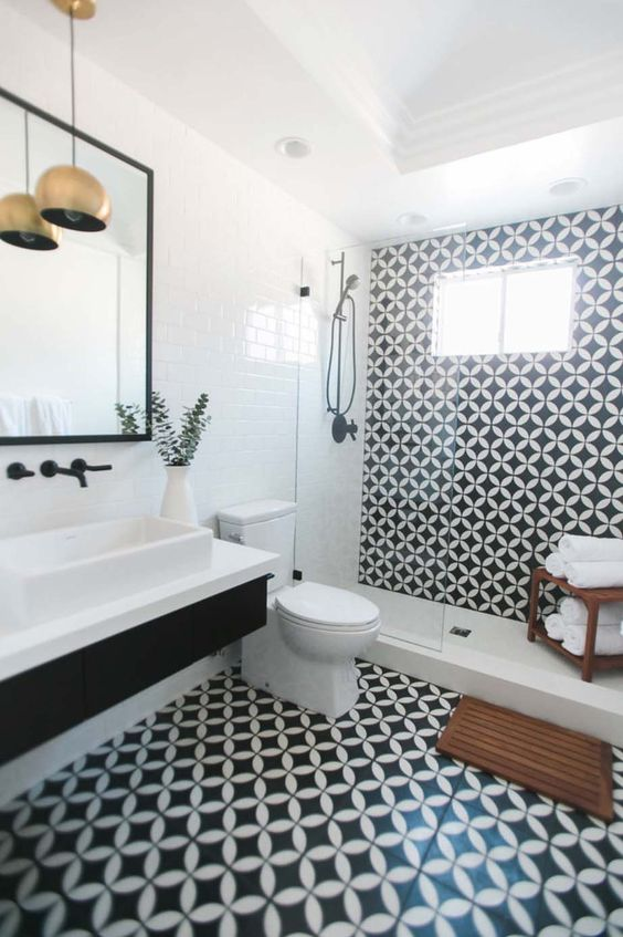 a monochromatic bathroom with black and white tiles, a black floating vanity and white appliances plus brass lamps