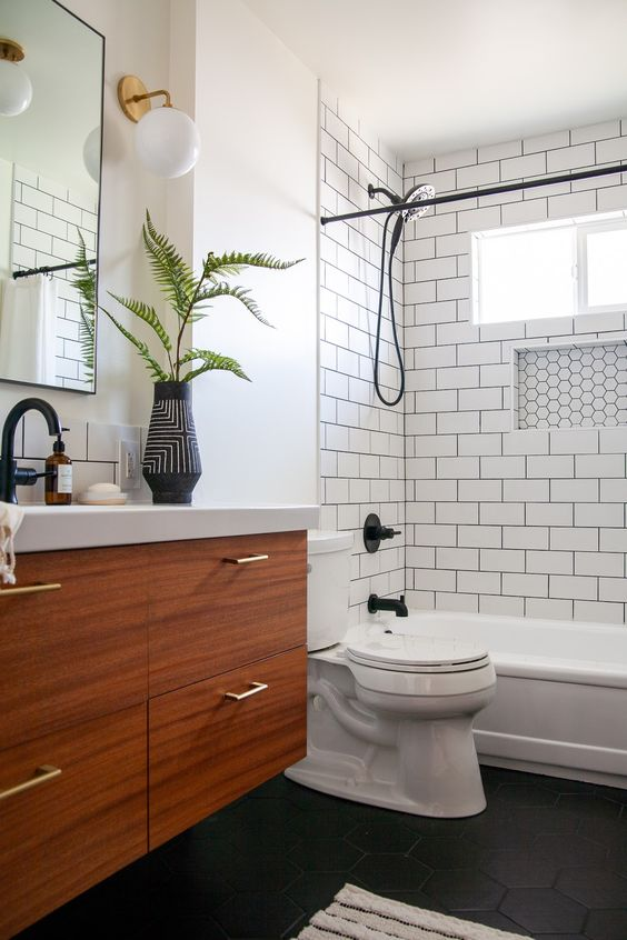a monochromatic bathroom with white subway tiles and black hex ones, a wooden vanity and black fixtures for a bolder look