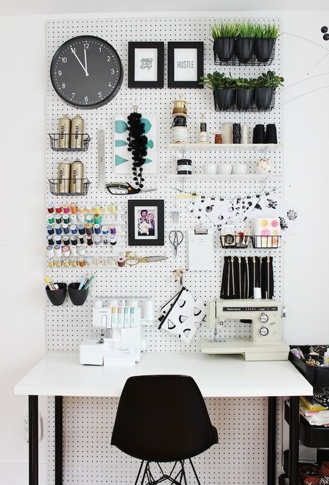 a monochromatic space with a pegboard done with shelves, wire baskets, containers and hooks
