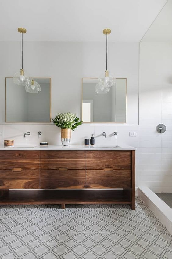 a neutral mid-century modern bathroom with white and mosaic geo tiles, a wooden vanity and chic pendant lamps plus mirrors in gold frames