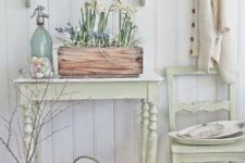 a neutral shabby chic entryway with pastel furniture – a chair, a console, a shelf, a box with blooms and a basket