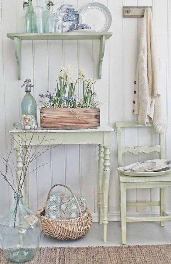 a neutral shabby chic entryway with pastel furniture - a chair, a console, a shelf, a box with blooms and a basket