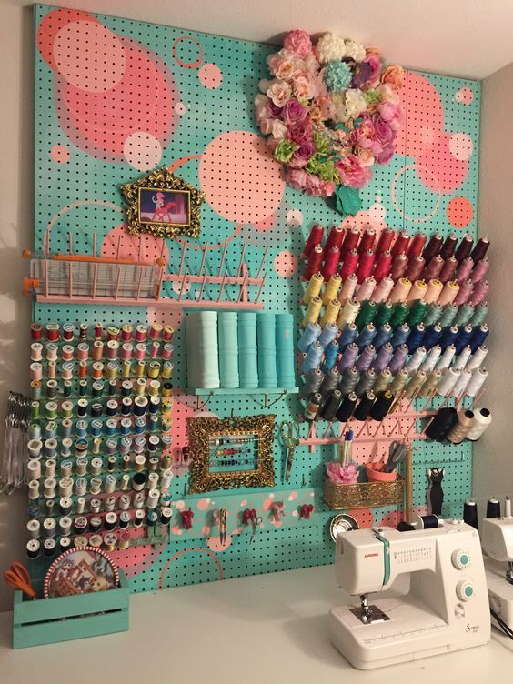 a painted pegboard with shelves, ledges, hooks and other stuff for sewing supplies