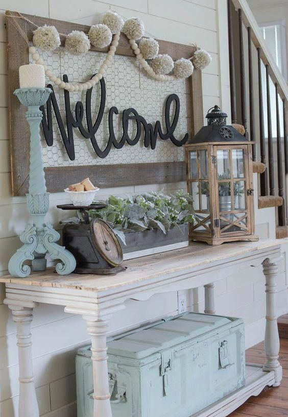 a pastel shabby chic entryway with a console table, a lantern with a pot, greenery in a box, a large chest, a candleholder and a sign with pompoms