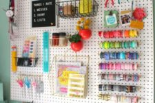 a pegboard done with various shelves, ledges, hooks and hangings plus plastic containers on the desk