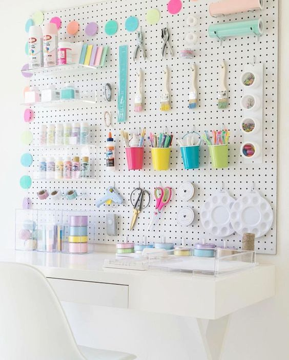 a pegboard spruced up with colorful cups, containers, hooks, acrylic ledges and other stuff
