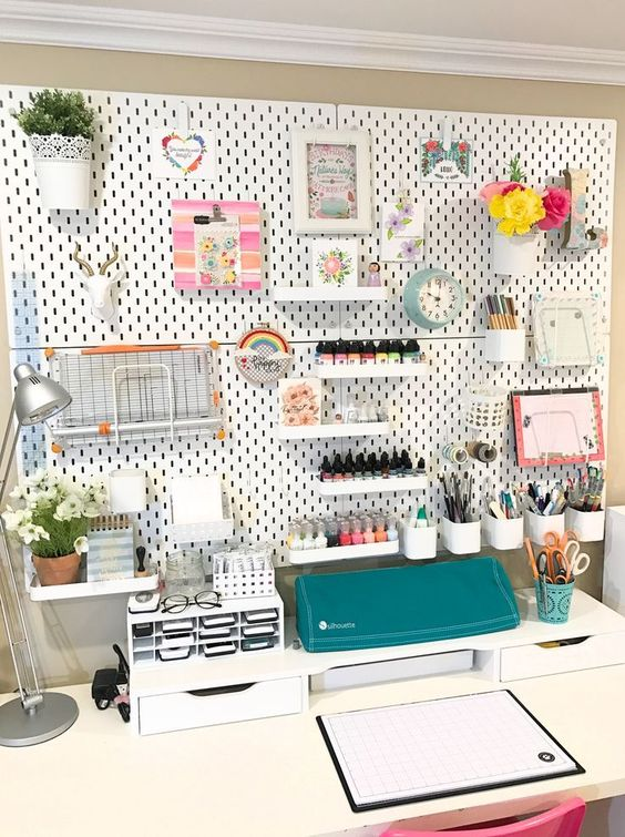 a pegboard with lots of shelves, storage containers and even planters attached to it