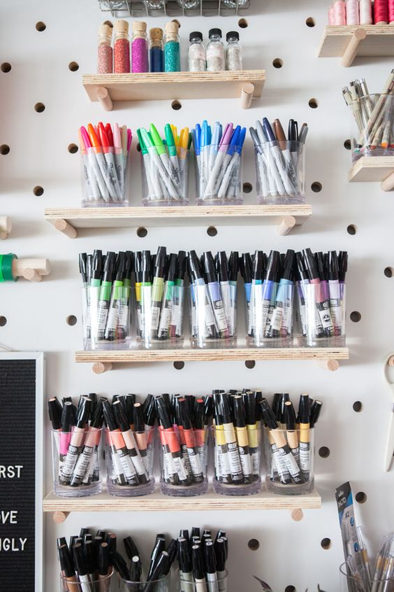 a pegboard with shelves and glasses with markers will help you organize them all