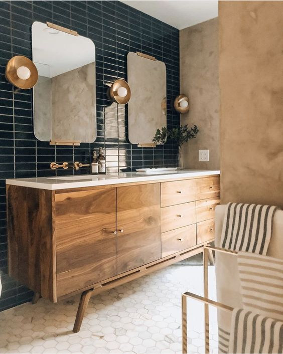 a refined mid-century modern bathroom with ran plaster walls, a wooden vanity, marble hex tiles and a navy skinny tile wall plus brass touches