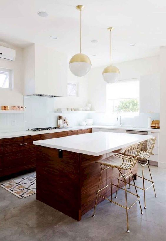a rich-stained mid-century modern kitchen with white countertops, a white hood and pendant sphere-shaped lamps
