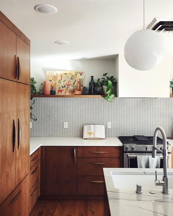 a rich-stained wood mid-century modern kitchen with white countertops, a graphic tile backsplash