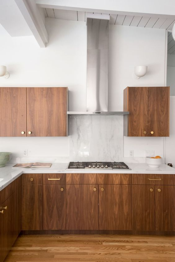 a rich-stained wood mid-century modern kitchen with white countertops, a white stone backsplash