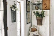 a shabby chic entryway with a dresser, potted greenery and blooms, a whitewashed chair, artworks
