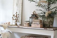 a shabby chic entryway with a long console table, a chest under it, a stool, a shutter, candelabras and candle lanterns