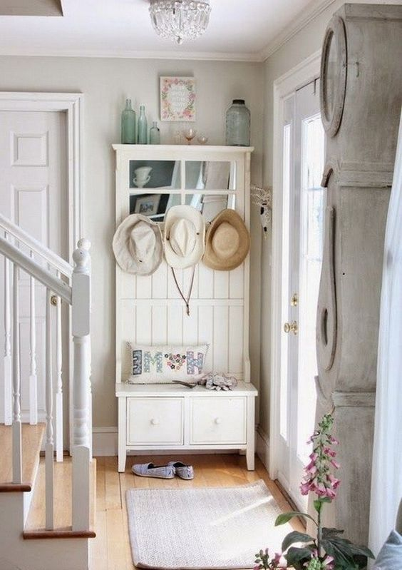 a shabby chic entryway with a storage unit with a seat, a rug, bottles and a whitewashed floor clock