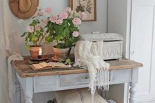 a shabby chic entryway with a wardrobe, a whitewashed console with a wooden top, a basket, potted blooms and art