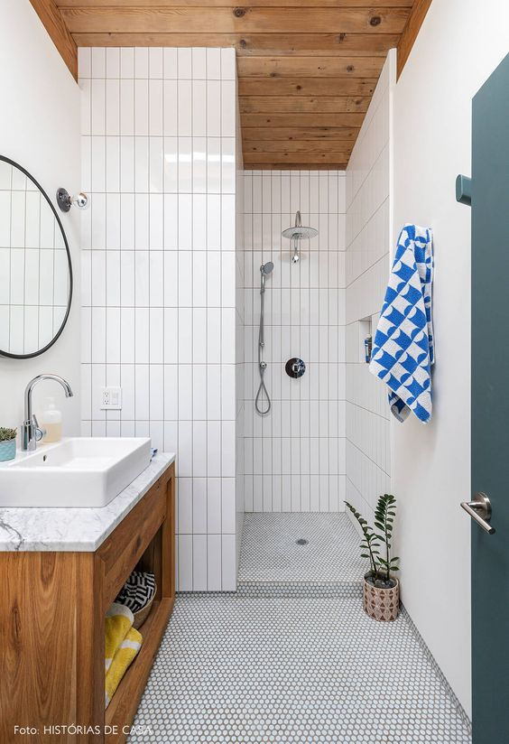 a simple mid-century modern bathroom with white penny and skinny tiles, a wooden vanity and ceiling and a round mirror