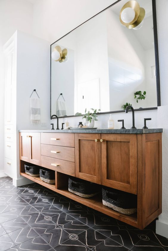 a stylish mid-century modern bathroom with black mosaic tiles, a large wooden vnaity with a stone countertop and touches of gold