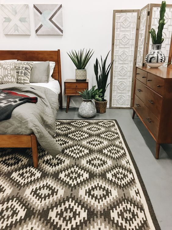 a stylish mid-century modern bedroom with a geometric rug, rich-stained furniture, potted greenery and artworks