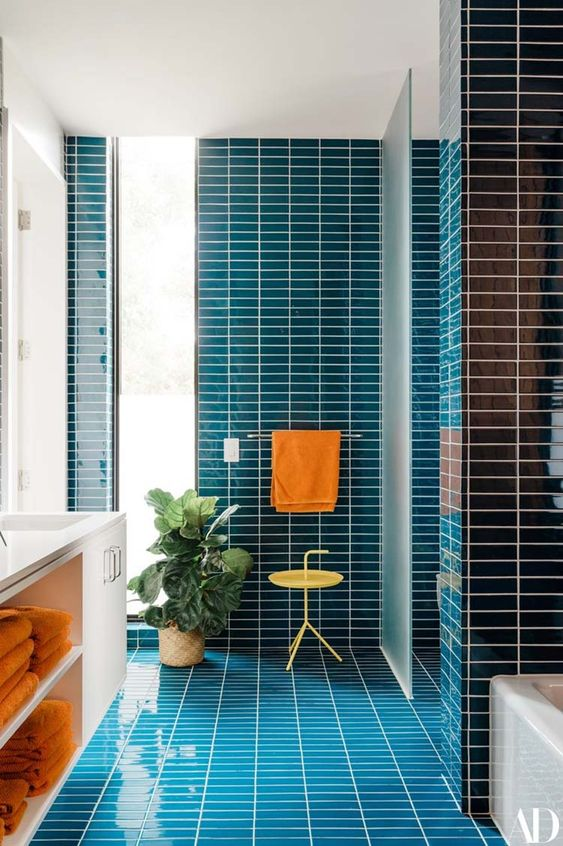a vibrant mid-century modern bathroom clad with navy skinny tiles, a white flaoting vanity and touches of orange