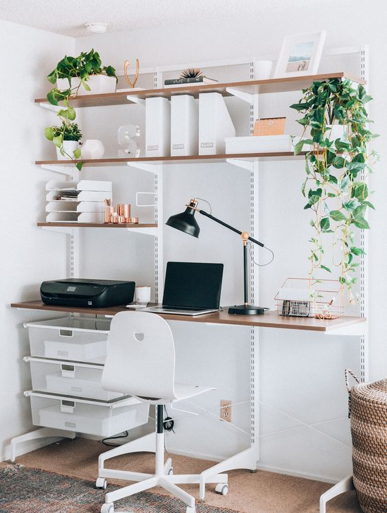 a wall mounted shelving unit with lots of shelves and boxes for storage plus a built in desk