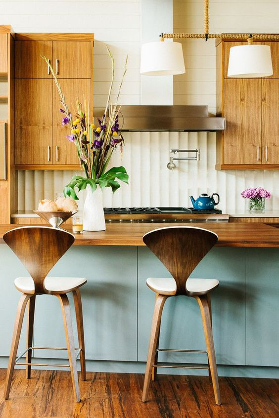 a welcoming mid-century modern kitchen with light-colored cabinets with metallic handles, plywood stools, a blue kitchen island and a wooden countertop