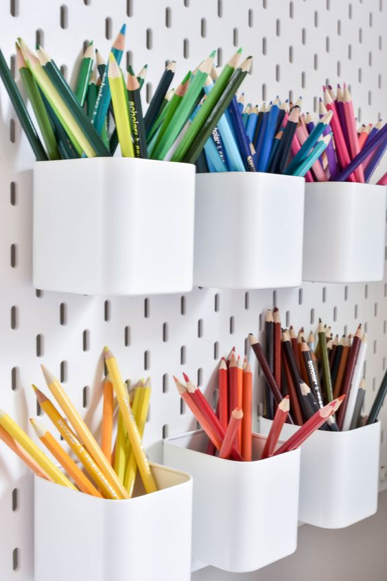 a white pegboard with pen holders is a cool idea for those who draw or write much