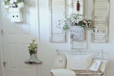 a white shabby chic entry with a metal bench, potted blooms and greenery, shutters on the wall and signs