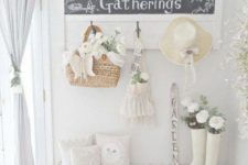 a white shabby chic entryway with a chic chalkboard sign, a whitewashed bench, blue curtains and baskets