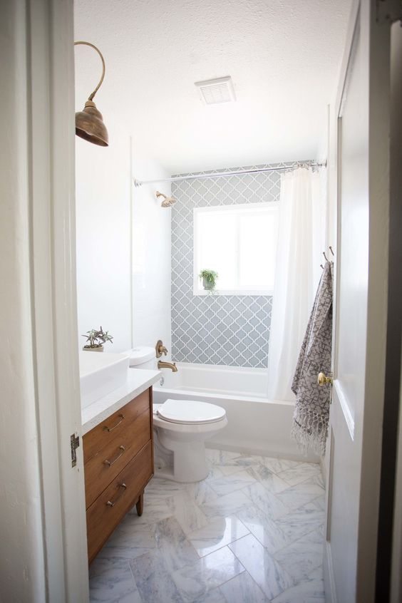 an airy mid-century modern bathroom with grey Moroccan tiles, white marble ones, a wooden vanity and touches of brass