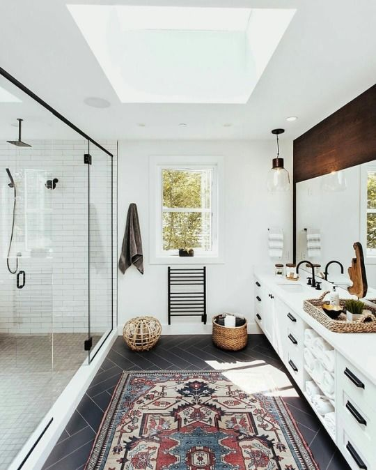 an airy mid-century modern bathroom with white tiles, a skylight, a boho rug, a large vanity with a wooden top and a large shower space with windows