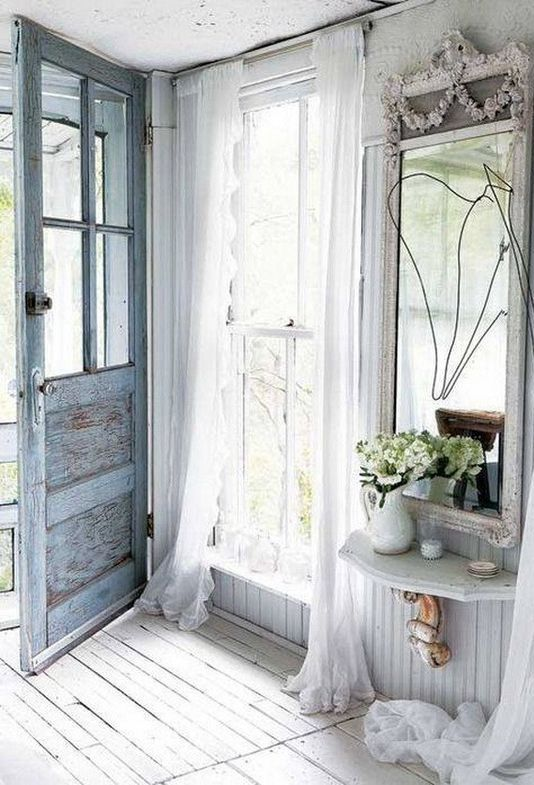 an airy shabby chic entryway with a blue door, a large mirror, a floatign shelf, tulle curtains and some blooms