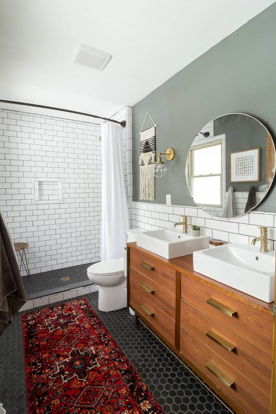 an amazing mid-century modern bathroom with white subway tiles and black hex ones, a bright rug and a wooden vanity with gold touches