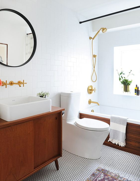 an elegant mid-century modern bathroom with white penny and subway tiles, rich stained furniture, black and gold touches