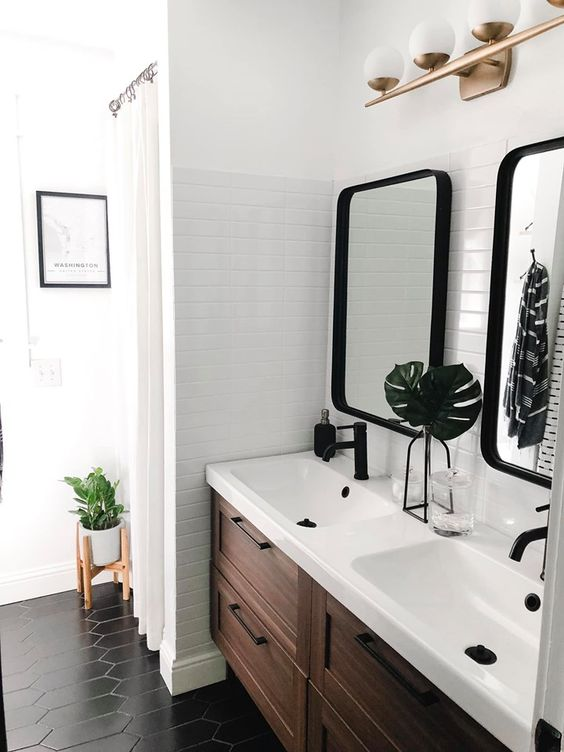 an elegant mid-century modern bathroom with white tiles, a wooden vanity, black tiles on the floor and black fixtures