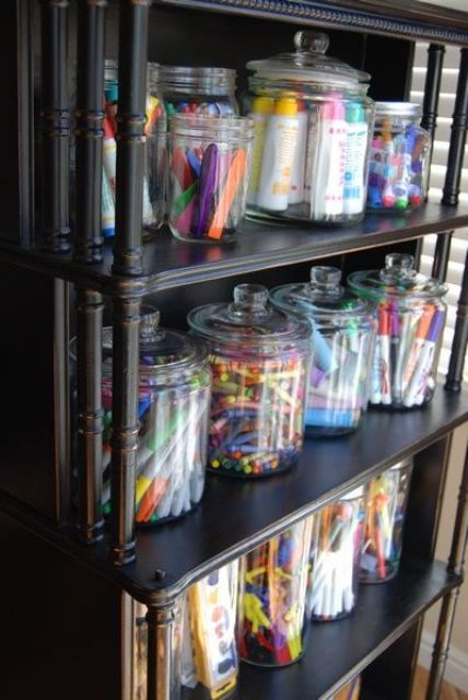 an open storage unit with large jars that are great to store crayons and markers