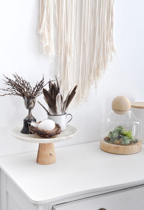 Scandinavian boho decor with a stand with a fake nest and egg, feathers and willow plus moss in a jar