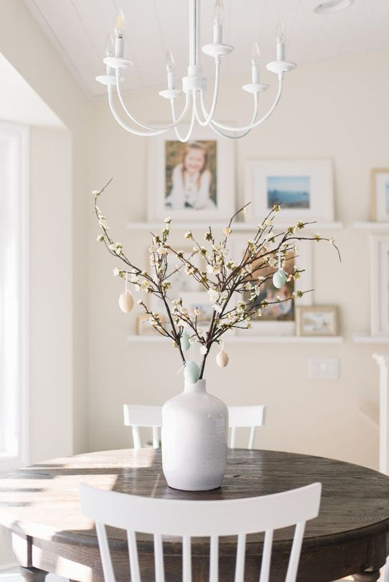 a Scandinavian Easter tree - white vase with blooming branches and pastel fake eggs is very chic