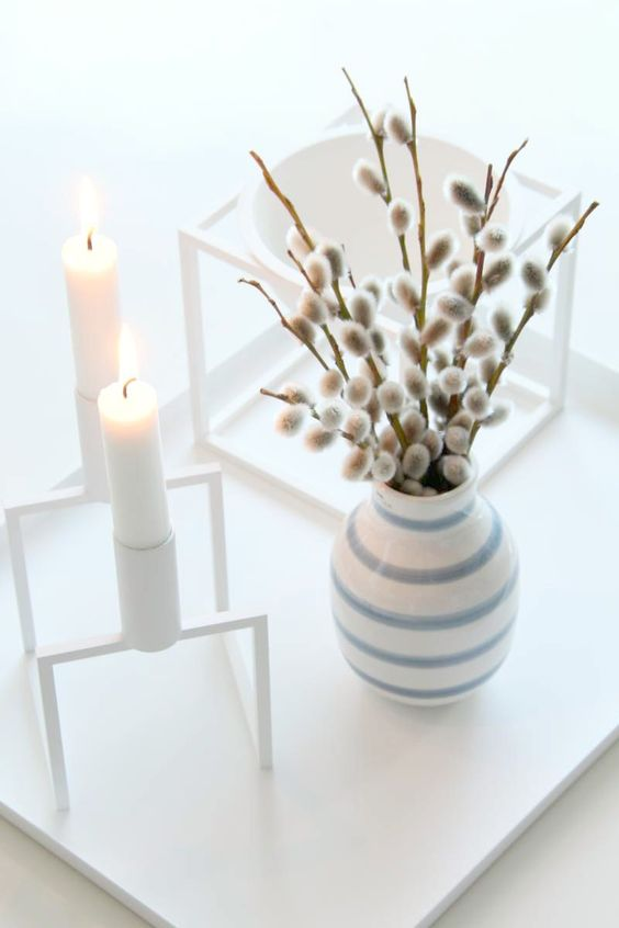a Scandinavian spring decoration with a framed candleholder, a striped vase with willow and a bowl