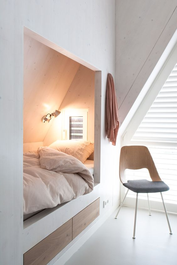 a built-in attic sleeping space with two sleek drawers for storage is amazing for having a cozy nap here