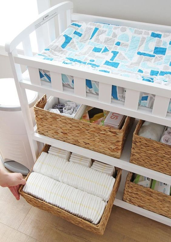 a changing table with basket boxes to store all the necessary stuff to change diapers