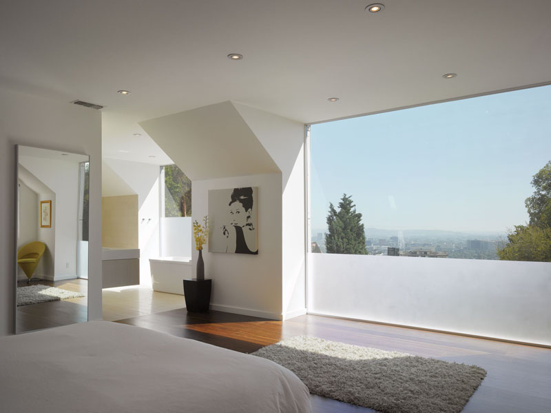 a contemporary bedroom with a laconic interior and a panoramic window with partial frosting to keep it more private