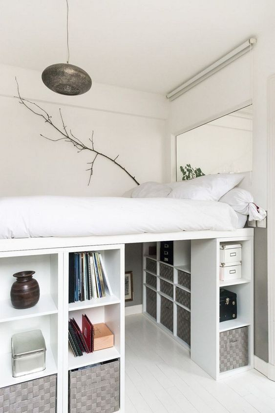 a creative tiny bedroom with a platform bed placed on storage units that create a whole wardrobe under it