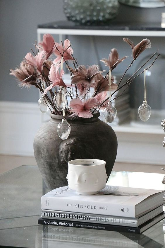 a dark vase with branches with pink and mauve feathers and glass egg ornaments with feathers inside