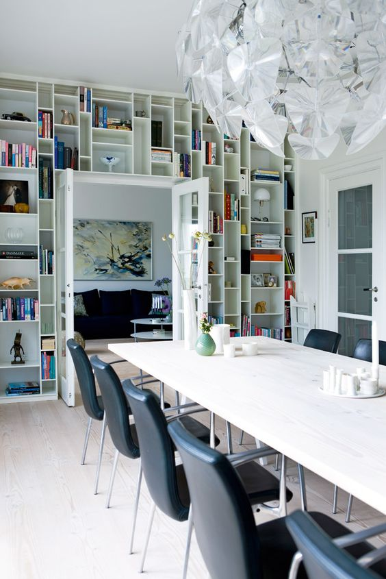 a dining room with a doorway wall taken by open shelves and displaying books, art and candleholders is a cool idea for saving space