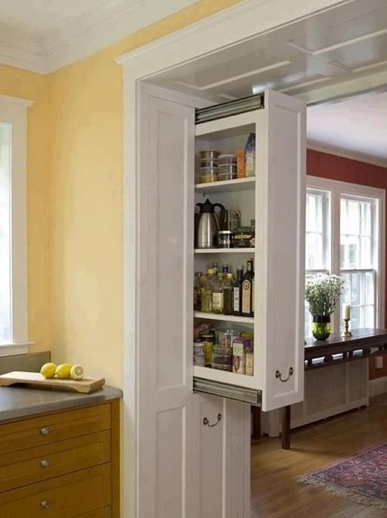 a doorway in the kitchen with hidden drawers built-in is a very cool idea to declutter the room and organize a small pantry right here