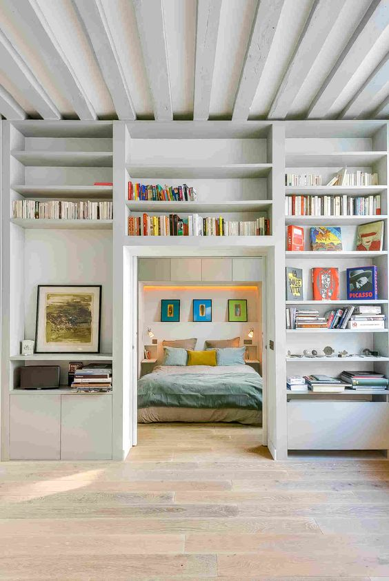 a doorway surrounded with open shelves used for storing books and artworks is a very cool idea to go for