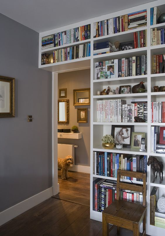 a doorway wall covered with open shelves that contain lots of books is a cool idea to organize your home library without wasting a lot of space