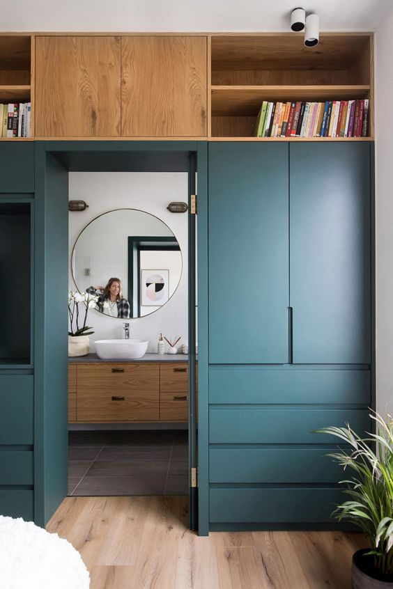 a doorway wall covered with sleek cabinets and drawers, open shelves will let you store a lot of things and not clutter the bedroom