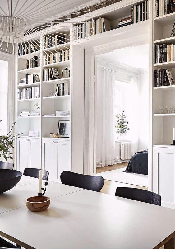 a doorway with open shelves and cabinets surrounding it is a cool idea to store a lot of things without buying separate storage units here and there
